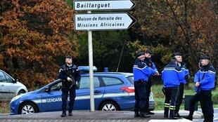 Gendarmes stand guard on a road near a retirement home for missionaries in Montferrier-sur-Lez after a hooded man wielding a knife murdered a woman.