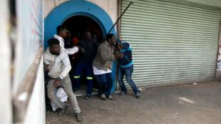 Des migrants nigérians se protègent d'une attaque de manifestants devant une église à Pretoria, le 18 février 2017.