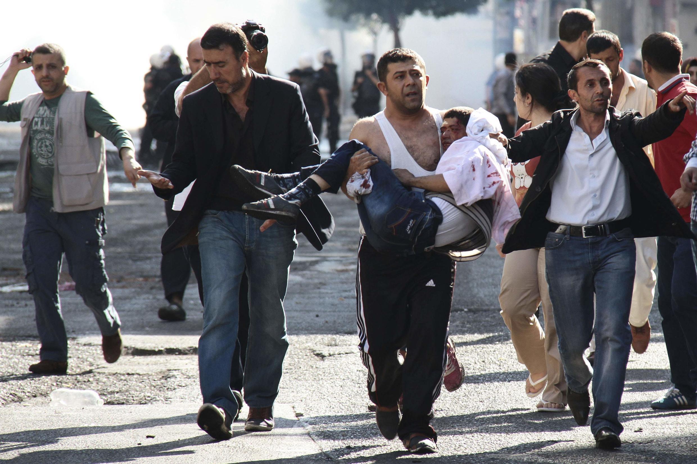 La répression policière est toujours féroce. Ici des manifestants kurdes transportent un blessé, le 8/10/14 à Diyarbakir en Turquie.