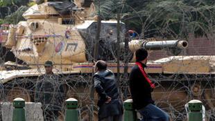 A soldier looks on as protesters gather in front of the presidential palace in Cairo, 11 February 2011.