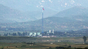 A North Korean flag flutters on top of a tower at the propaganda village of Gijungdong in North Korea, in this picture taken from Tongil observatory in Paju