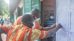 Voters check the electoral register posted at a primary school in Cotonou on 17 May 2020.