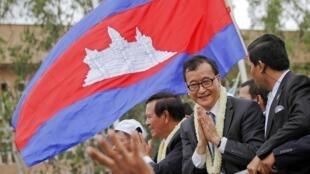 Sam Rainsy, chef du principal parti d'opposition, salue ses partisans à Phnom Penh, le 19 juillet 2013.
