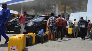 Des dizaines de personnes font la queue à une station essence de Lagos avec leur jerrican, en mai 2015. Les pénuries de carburants pèsent lourdement sur l'économie du pays,