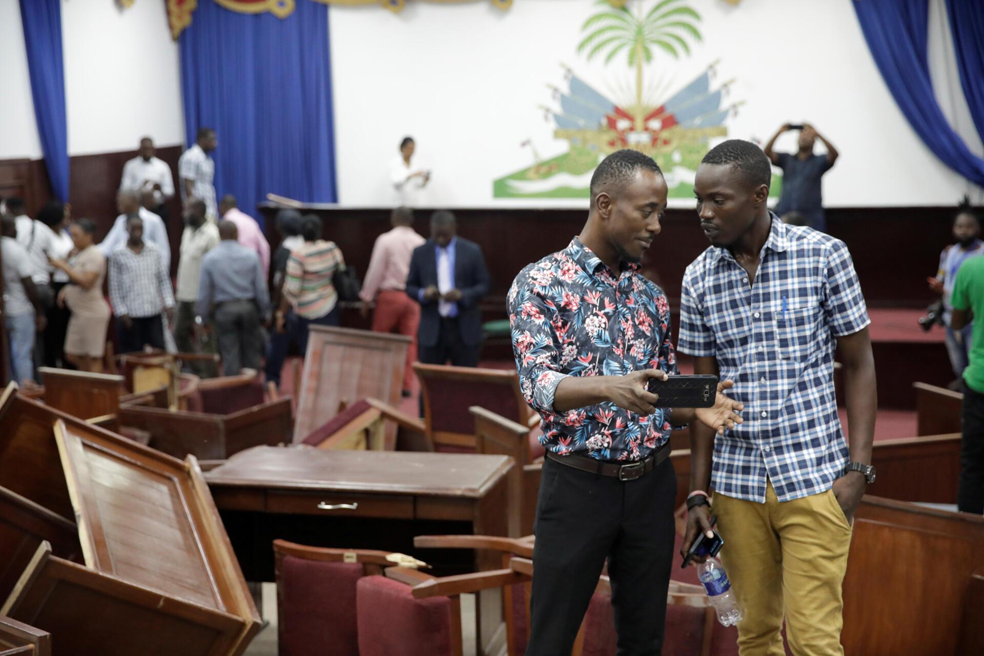 Des journalistes haïtiens filment le Parlement après avoir été saccagé par des députés de l'opposition, selon les médias locaux, à Port-au-Prince, le 3 septembre 2019.