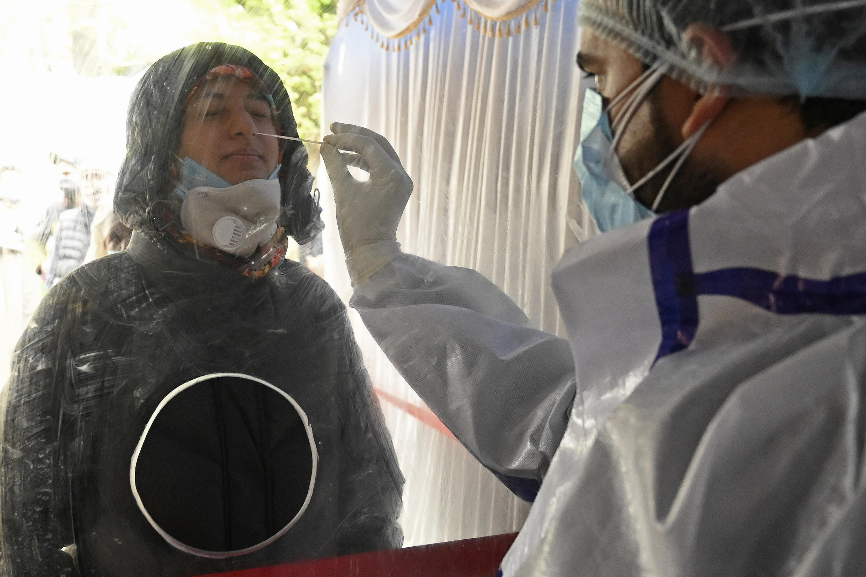 Un técnico sanitario toma una muestra de mucosa a una persona para una prueba de detección del coronavirus, el 15 de abril de 2021 en Srinagar, al norte de India