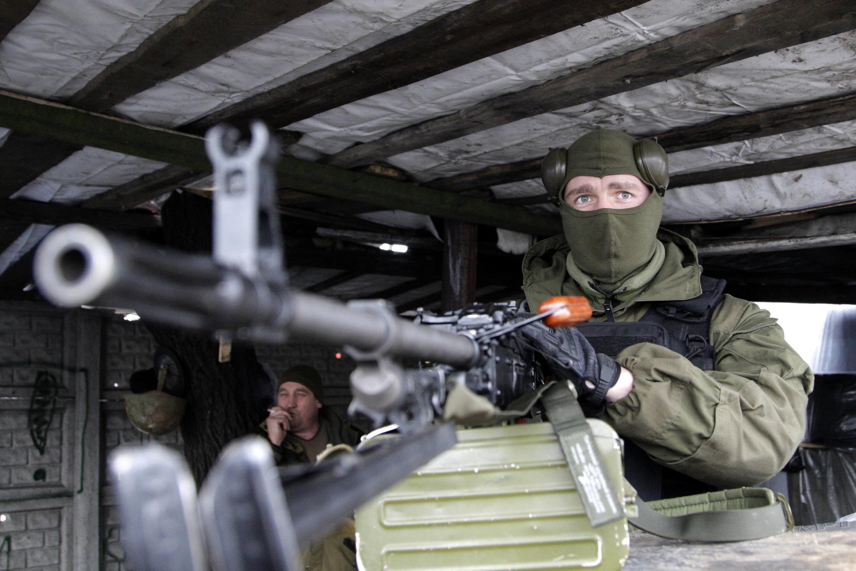 Separatista faz a segurança de posto de controle pró-russo em Donetsk.