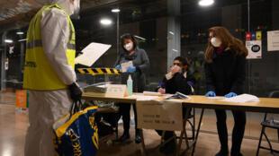 Un empleado de correos entrega los votos por correo a los funcionarios tras el cierre de un colegio electoral en el mercado del Ninot de Barcelona, España, durante las elecciones autonómicas el 14 de febrero de 2021