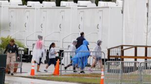 Niños caminan junto a un guardia de seguridad, en el centro de cuidado de Homestead, Florida, el albergue más grande de EE.UU. para niños inmigrantes, el pasado 13 de febrero de 2019.