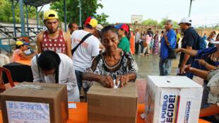 Une Amérindienne Guajiro dépose son bulletin de vote, lors du référendum convoqué par l'opposition contre le gouvernement de Nicolas Maduro, à Maracaibo (Venezuela), le 16 juillet 2017.