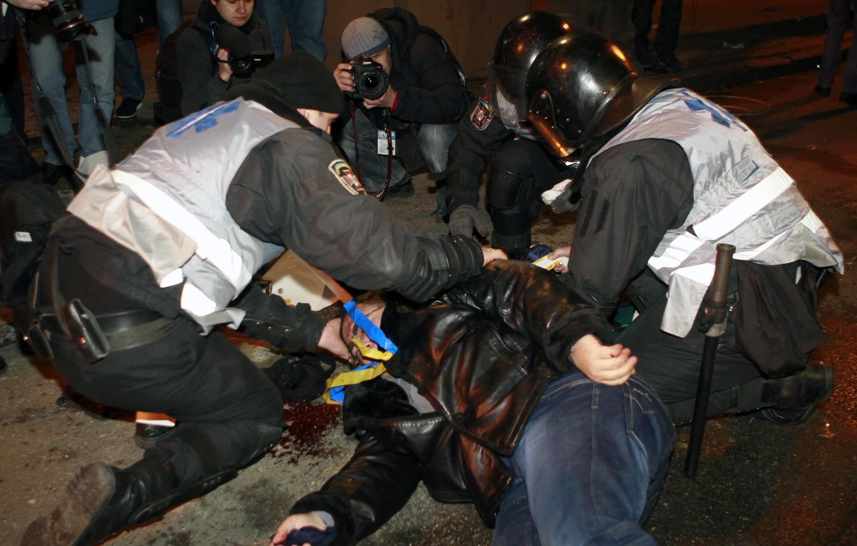 Милиционеры оказывают первую помощь раненому