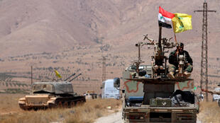 Cờ của Hezbollah bên cạnh cờ Syria trên một chiếc quân xa ở vùng  Qalamoun phía Tây. Ảnh ngày 28/08/2017.