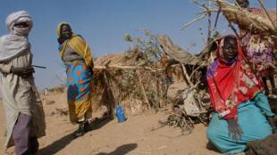 Réfugiés soudanais devant l'abri qu'ils ont construit à Djoran, dans le canton de Birak, au Tchad