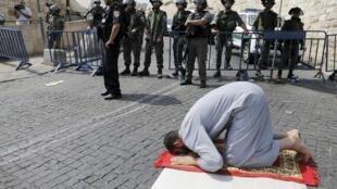 Um palestino ora em frente de uma barreira de policiais israelenses, perto do bairro árabe de Wadi al-Joz, em Jerusalém Oriental