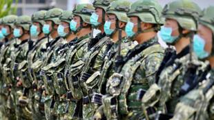 Soldados taiwaneses con mascarilla permanecen formados durante un discurso de la presidenta del país, Tsai Ing-wen, en una visita a la base militar de Tainan, al sur de Taiwán, el 9 de abril de 2020
