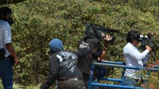 Au Honduras, un manifestant lance une pierre sur un journaliste reporter d'images, à Tegucigalpa, le 25 mars 2015.