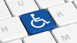 Bouton bleu avec le signe de fauteuil roulant sur un clavier d'ordinateur