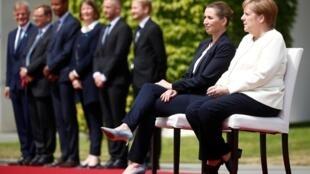 德国总理默克尔在欢迎到访的丹麦首相时罕见地改为坐着参加奏国歌仪式。