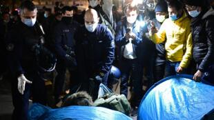 Полицейские эвакуируют стихийный лагерь мигрантов на площади Республики вечером в понедельник, 23 ноября 2020.