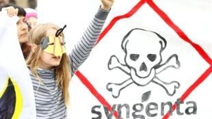 """Una niña enmascarada manifesta durante la """"Marcha contra Bayer & Syngenta"""". Basilea, Suiza, 18 de mayo de 2019."""