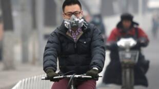 北京街頭戴着口罩的騎車人2014年2月24日。