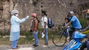A une vingtaine de kilomètres au sud d'Antananarivo, sur la nationale 7, les autorités sanitaires et la police contrôlent la température des passants, le 27 mars 2020.