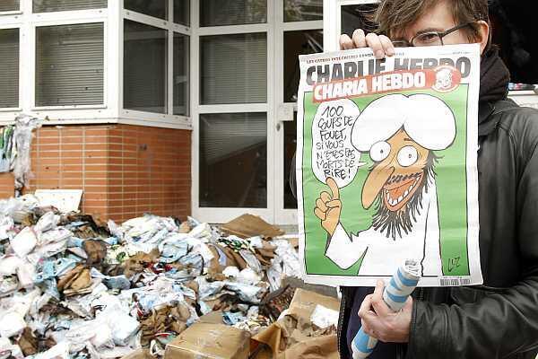 El dibujante Luz sostiene el número de 'Charlie Hebdo' rebautizado 'Charia Hebdo' delanta de las oficinas quemadas de la publicación, el 2 de noviembre de 2011 en París.
