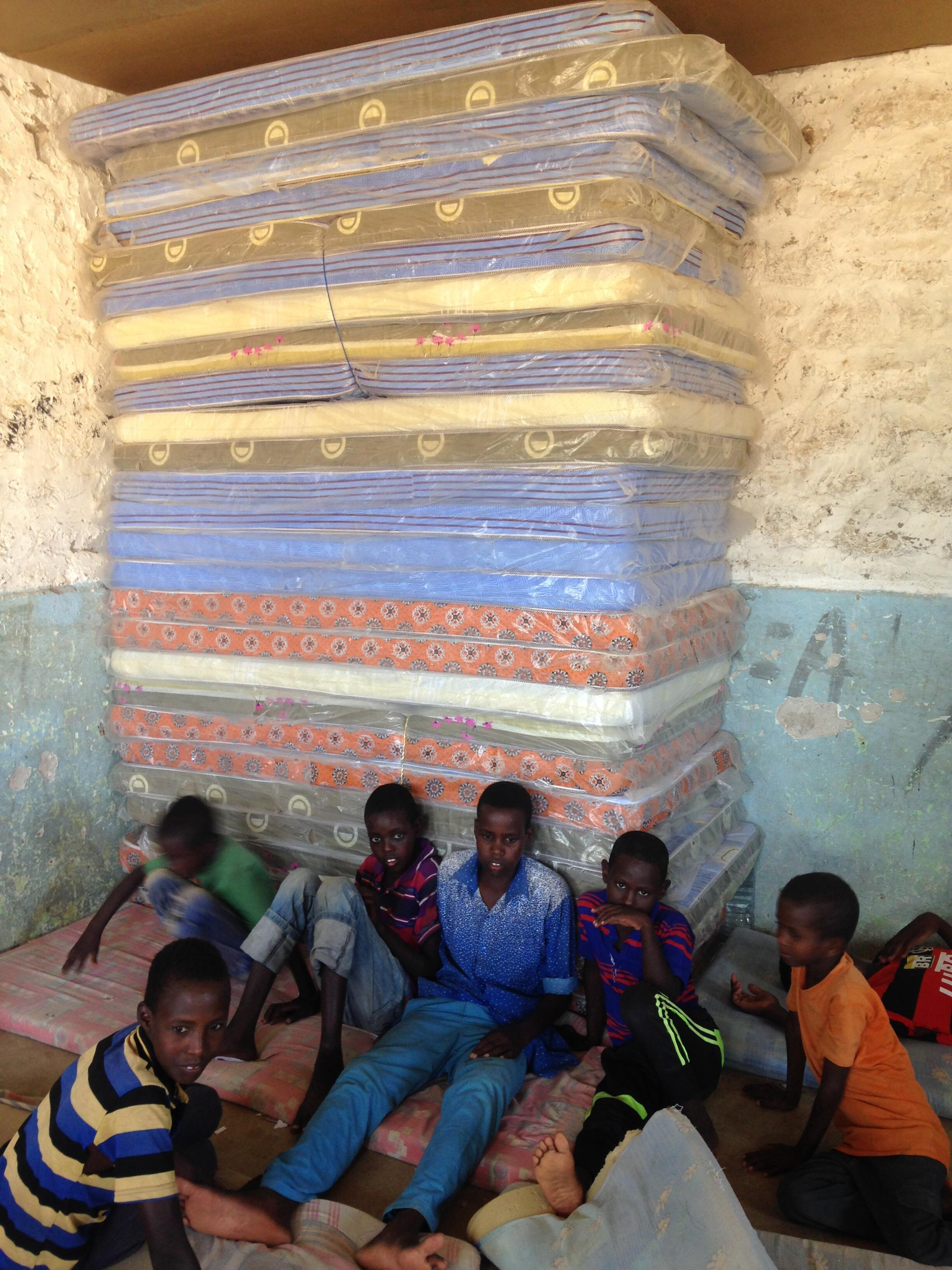 Schoolboys in rural Somaliland relax among mattresses in their classroom/dormitory