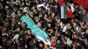 Palestinians carry the body of Arafat Jaradat as it arrives at his home before his funeral in the West Bank village of Sa'ir, 25 February, 2013