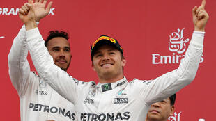 Mercedes' drivers Nico Rosberg of Germany and Lewis Hamilton of Britain attend an awarding ceremony after the race