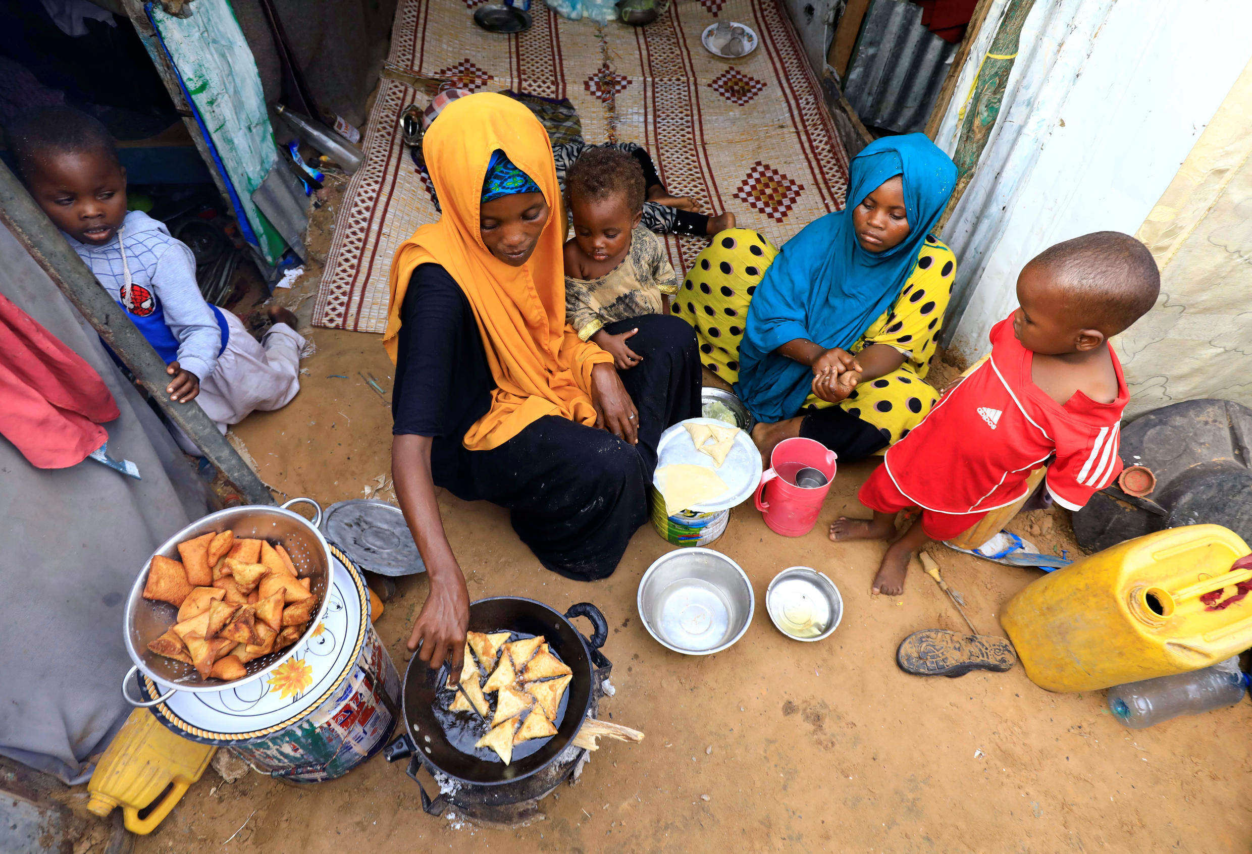 An internally displaced Somali woman and her children prepare their Iftar meal during the month of Ramadan at the Shabelle makeshift camp in Hodan district of Mogadishu, Somalia April 24, 2020.