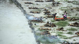 Municipal corporation workers prepare to cremate a body buried in a shallow grave on the banks of the Ganges river during the Covid-19 pandemic
