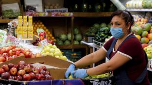 Una vendedroa del mercado Central de Abastos de la ciudad mexicana de Guadalajara coloca unas manzanas el 1 de abril de 2020