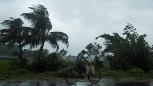 Un hombre en bicicleta bajo la lluvia, antes de la llegada del ciclón Amphan, el 20 de mayo de 2020 en Midhapore, India