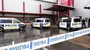 Vans da polícia são vistas em frente ao centro comercial Herman, onde o Savo Vocational College está localizado em Kuopio, Finlândia, 1 de outubro de 2019.