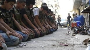 Des combattants de l'ASL en pleine prière à Alep, le 9 juillet 2013.