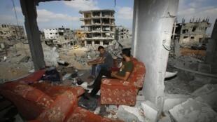 Des habitants assis au milieu de ce qu'il reste de leur maison, dans l'est de Gaza, le 27 août 2014.