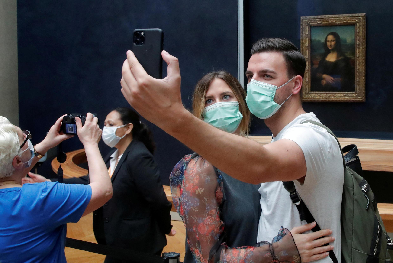 Turistas tiram fotos em frente à Mona Lisa, no Museu do Louvre, reaberto ao público desde o início de julho, em Paris. (06/07/2020)