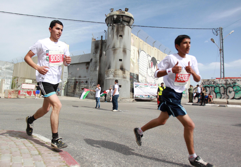 Athlètes palestinien et étranger, le 27 mars 2015, le long du mur de séparation lors du 3e marathon palestinien à Bethléem.