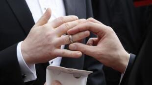 Échange d'alliances lors d'un mariage entre deux hommes.