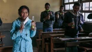 Wasu dalibai a kasar Madagascar yayin shan tsimin gargajiya na Covid-Organics da shugaban kasar Andry Rajoelina yace magani ne kuma rigakafin cutar coronavirus.