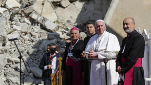 Pope Francis, surrounded by shells of destroyed churches, attends a prayer for the victims of war with Mosul and Aqra Archbishop Najib Mikhael Moussa, left, at Hosh al-Bieaa Church Square, in Mosul, Iraq, 7 March 2021.