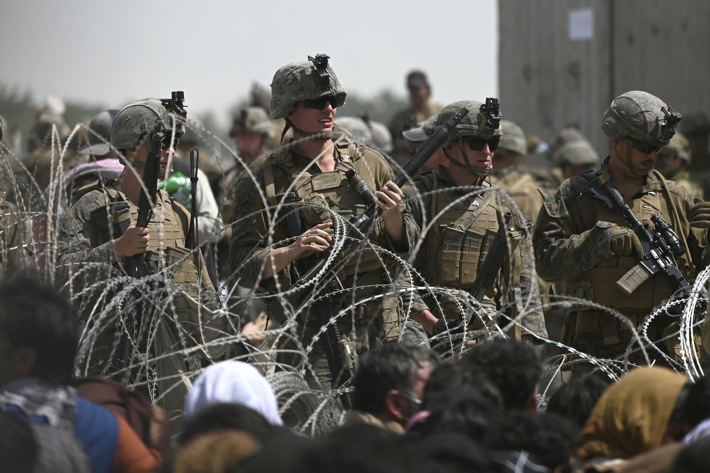 US soldiers stand guard behind barbed wire as Afghans sit on a roadside near the military part of the airport in Kabul on August 20, 2021, hoping to flee from the country