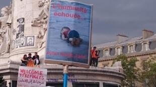 Фотография утонувшего сирийского мальчика Айлана Курди на митинге солидарности с мигрантами в Париже, 5 сентября 2015 года.