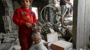Một bé gái giữa những căn nhà đổ nát tại Raqqa, Syria, ngày 12/10/2018. Làm sao xác định được tội ác của chế độ Assad?