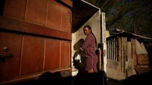 Une femme nettoie les toilettes d'un township de la ville de Graaff-Reinet (Afrique du Sud) en novembre 2019.