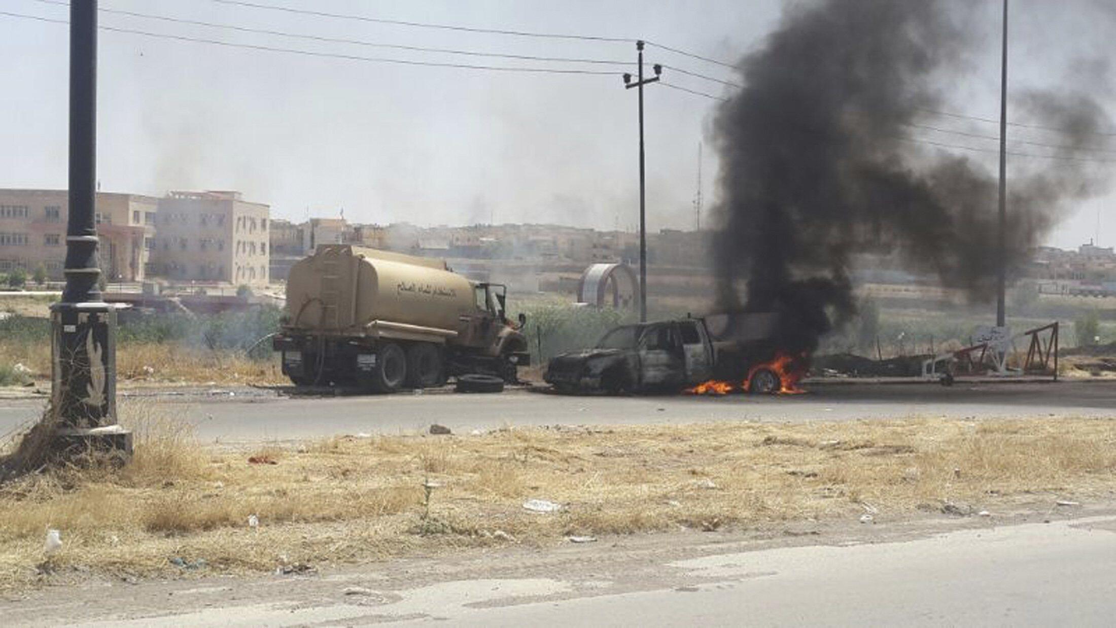 Автомобили сил безопасности Ирака, сожженные в столкновении с ИГИЛ в Мосуле 10/06/2014