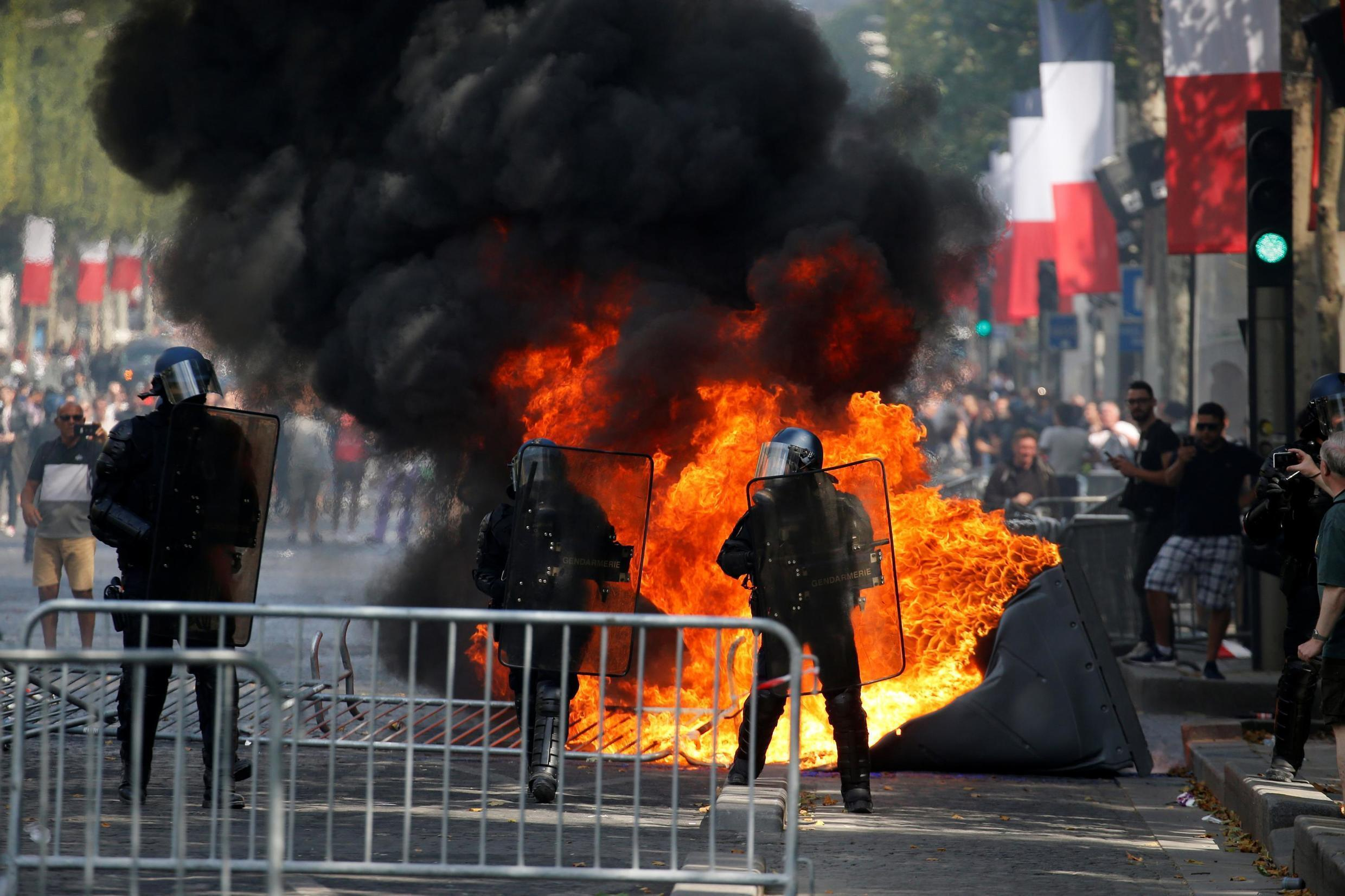 A portable toilet burns next to French Gendarmes during clashes with protesters on the Champs Elysees avenue after the traditional Bastille Day military parade in Paris, 14 July 2019.