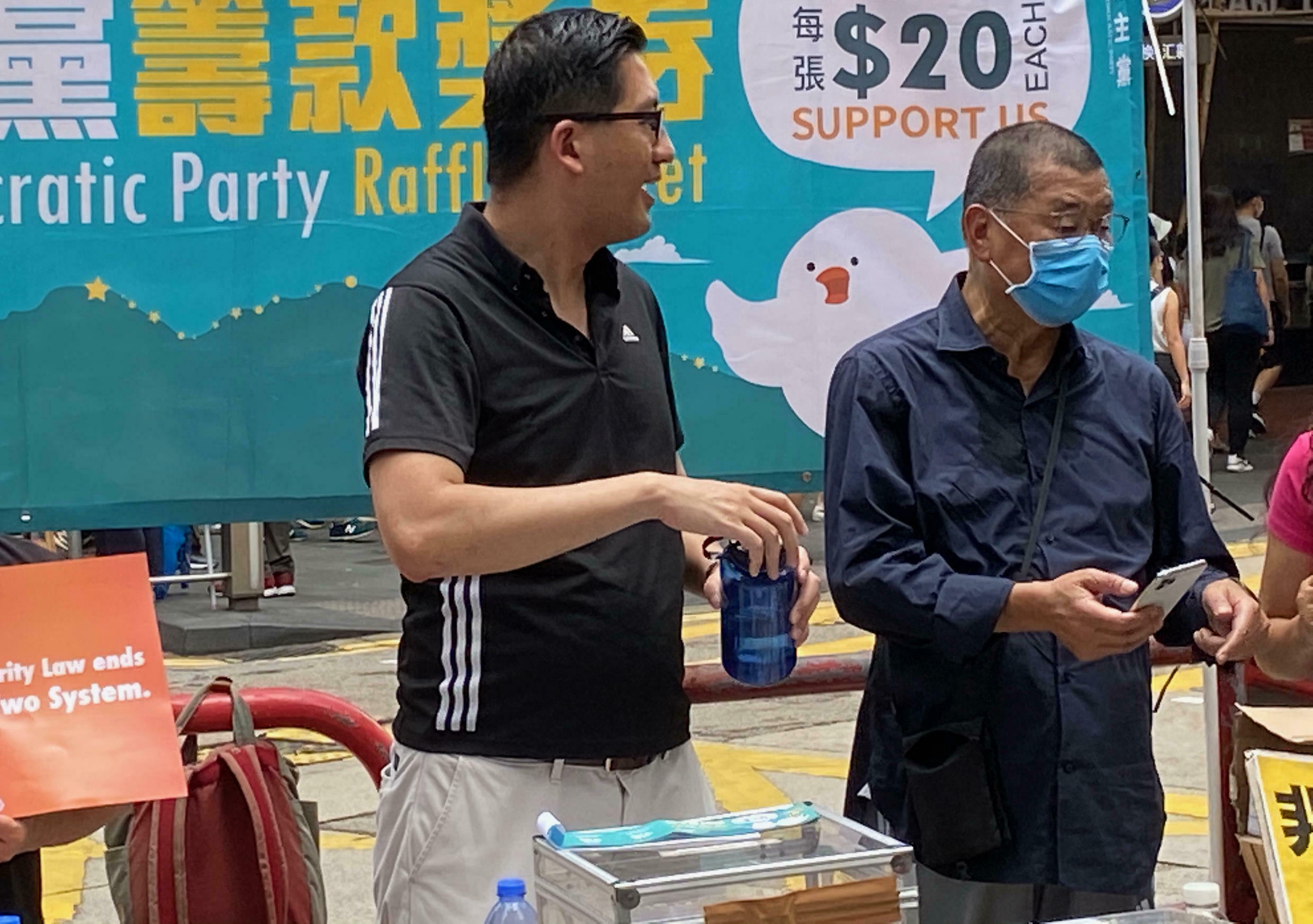 Jimmy Lai (right), pictured at a Democratic Party stand at a protest on 1July 2020, the day after Hong Kong's National Security Law came into force.