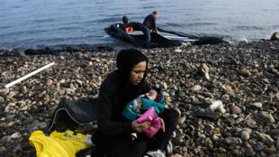 Une femme tient son bébé dans les bras, juste après avoir débarqué sur l'île grecque de Lesbos, lundi 19 octobre 2015.
